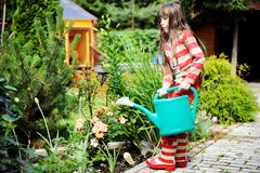 Little girl in a garden with green watering can Royalty Free Stock Image