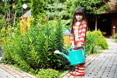 Little girl in a garden with green watering can Stock Photography