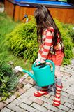 Little girl in a garden with green watering can Royalty Free Stock Photography