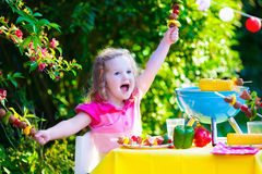 Little girl at garden grill party Royalty Free Stock Images