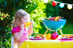 Little girl at garden grill party Royalty Free Stock Image