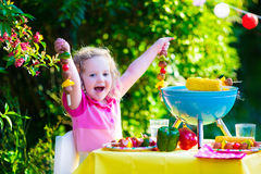 Little girl at garden grill party Stock Images
