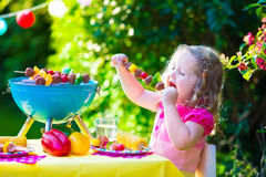 Little girl at garden grill party. Children grilling meat. Family camping and enjoying BBQ. Little girl at barbecue preparing steaks, kebab and corn. Kids eating Stock Photo