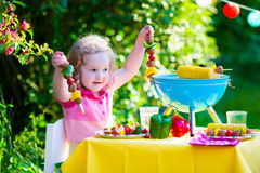 Little girl at garden grill party Royalty Free Stock Photos