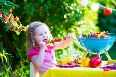Little girl at garden grill party Stock Photography