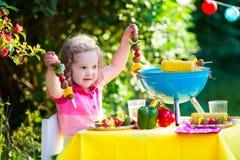 Little girl at garden grill party Stock Photos
