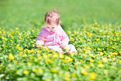 Little girl in garden with many yellow flowers Royalty Free Stock Image