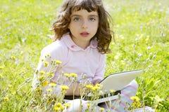 Little girl on garden meadow notebook computer Royalty Free Stock Photos