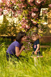 Little girl in garden with mother Stock Photos