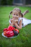 Little girl in garden with a plate of vegetables Stock Photo