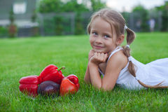 Little girl in garden with a plate of vegetables Royalty Free Stock Image
