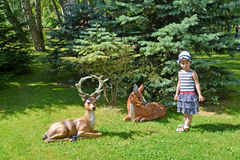 The little girl and garden sculptures of deer in a summer garden Royalty Free Stock Photography