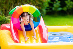 Little girl in garden swimming pool Royalty Free Stock Photos