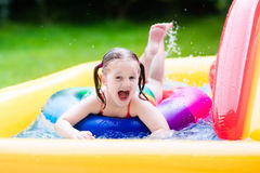 Little girl in garden swimming pool. Children playing in inflatable baby pool. Kids swim and splash in colorful garden play center. Happy little girl playing Stock Images