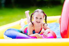 Little girl in garden swimming pool Stock Photography