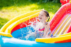 Little girl in garden swimming pool Royalty Free Stock Photography
