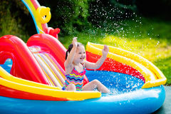 Little girl in garden swimming pool. Children playing in inflatable baby pool. Kids swim and splash in colorful garden play center. Happy little girl playing Stock Photo