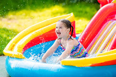 Little girl in garden swimming pool. Children playing in inflatable baby pool. Kids swim and splash in colorful garden play center. Happy little girl playing Stock Image