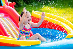 Little girl in garden swimming pool Royalty Free Stock Images
