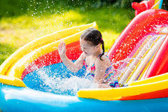 Little girl in garden swimming pool. Children playing in inflatable baby pool. Kids swim and splash in colorful garden play center. Happy little girl playing Stock Photos