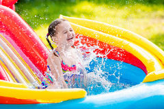 Little girl in garden swimming pool Royalty Free Stock Image