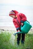 Little girl gardener. Watering flowers royalty free stock photo