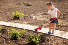 Little girl gardening in summer day Royalty Free Stock Photos