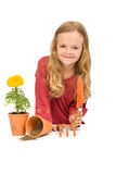 Little girl with gardening tools and potted flower Royalty Free Stock Photos