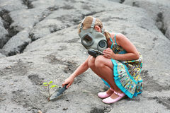 Little girl with gas mask. A conceptual picture of little with gas mask girl planting a tree on a rocky surface Stock Photos
