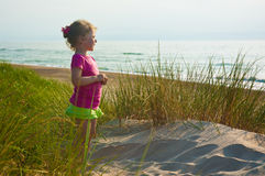 Little girl gazing at the sea. Girl standing on the sand among the high grass gazing at the sea Stock Photo