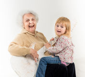 Little girl on geatgrandmother knees having fun Stock Image