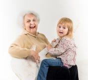 Little girl on geatgrandmother knees having fun Stock Image