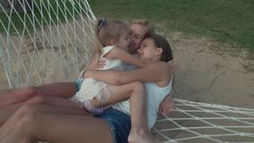 Little girl gently hugs mom and sister in hammock slow motion stock footage video stock footage