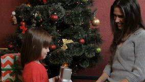 Little girl gets the christmas gift from her mother stock video footage