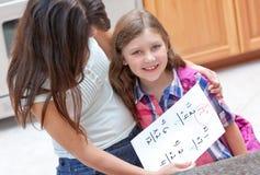 Little girl gets good grade on her homework. Proud mom hugs her little girl who gets good grade on her homework Royalty Free Stock Image