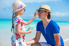 Little girl gets sun cream on her dad's nose Royalty Free Stock Images