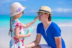 Little girl gets sun cream on her dad's nose Royalty Free Stock Photo
