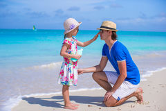 Little girl gets sun cream on her father's nose Royalty Free Stock Photos