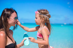 Little girl gets sun cream on her mother's nose Stock Image