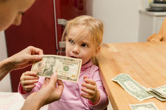 Little girl gets ten dollars from her mother. Concept of pocket money for a little girl Royalty Free Stock Photography