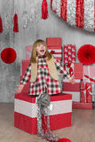Little girl gets up from a big gift box in white-red studio Royalty Free Stock Photography