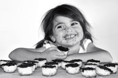 Little girl getting caught eating chocolate cookies Stock Photos