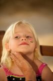 Girl Face Painting. Little girl getting a flower painted on her cheek Royalty Free Stock Photo