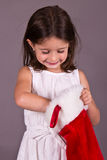 Little girl getting a gift from her Christmas stocking. A little girl getting a gift from her Christmas stocking Stock Photo