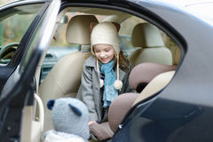 Little girl getting into her car seat Royalty Free Stock Photos
