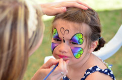 Little girl getting her face painted Stock Image