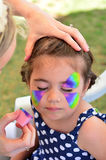 Little girl getting her face painted Royalty Free Stock Photos