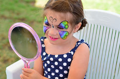 Little girl getting her face painted Stock Photos