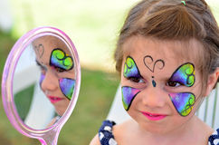 Little girl getting her face painted. Little girl getting with face looks at the mirror. Focus on face royalty free stock photography