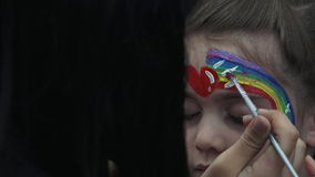 Little girl getting her face painted with rainbow by face painting artist stock video footage